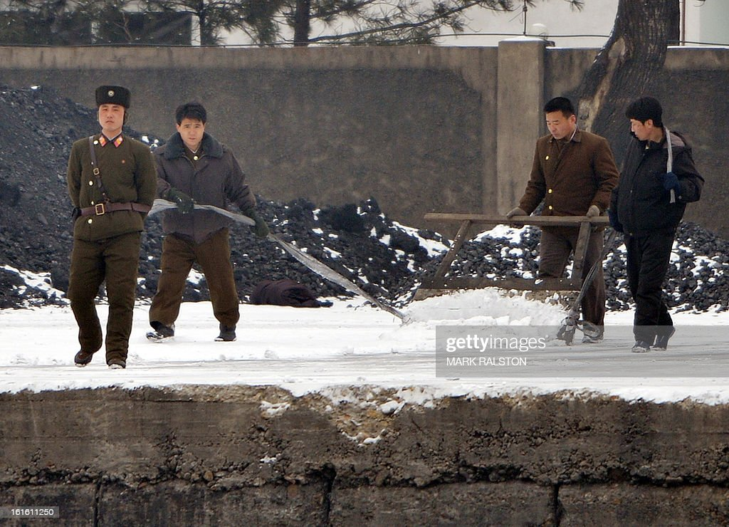 A North Korean soldier patrols beside men removing snow on the banks of the Yalu River at the North Korean town of Sinuiju across from the Chinese city of Dandong on February 13, 2013. While the rest of the world reacted with outrage, North Koreans were swept up in a 'storm of excitement' over their country's latest nuclear test, state media reported. The countries third nuclear test was widely condemned by the international community, led by the United States and the UN Security Council, which met in emergency session the same day. AFP PHOTO/Mark RALSTON