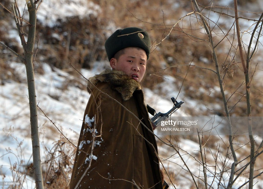 A North Korean soldier reacts as he patrols along the Yalu River near the North Korean town of Sinuiju after the country conducted it's third nuclear test on February 12, 2013 across from the Chinese city of Dandong. North Korea staged its most powerful nuclear test yet on February 12, claiming a breakthrough with a 'miniaturised' device in a striking act of defiance to global powers including its sole patron China. AFP PHOTO/Mark RALSTON