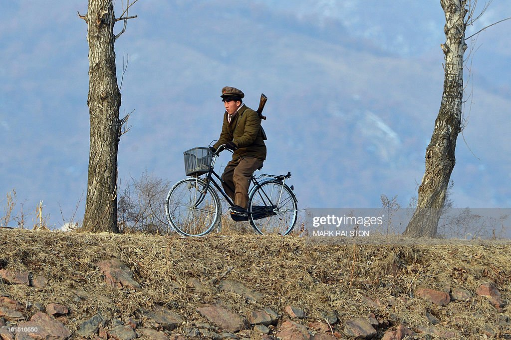 A North Korean soldier rides a bike beside a river crossing on the Yalu River near the North Korean town of Sinuiju after the country conducted it's third nuclear test on February 12, 2013. North Korea staged its most powerful nuclear test yet, claiming a breakthrough with a 'miniaturised' device in a striking act of defiance to global powers including its sole patron China. AFP PHOTO/Mark RALSTON