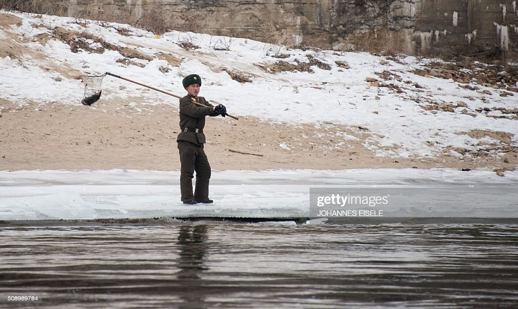 A North Korean soldier stands along the banks of the Yalu River after catching a fish in the North Korean town of Sinuiju, in an image taken from across the river in the Chinese border town of Dandong on February 8, 2016. The UN Security Council strongly condemned North Korea's rocket launch on February 7 and agreed to move quickly to impose new sanctions that will punish Pyongyang for 'these dangerous and serious violations.' With backing from China, Pyongyang's ally, the council again called for 'significant measures' during an emergency meeting held after North Korea said it had put a satellite into orbit with a rocket launch. AFP PHOTO / JOHANNES EISELE / AFP / JOHANNES EISELE