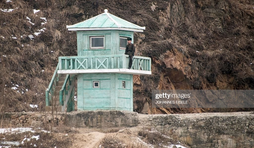 A North Korean soldier stands at a watchtower on the banks of the Yalu River in the North Korean town of Sinuiju, in an image taken from across the river in the Chinese border town of Dandong on February 8, 2016. The UN Security Council strongly condemned North Korea's rocket launch on February 7 and agreed to move quickly to impose new sanctions that will punish Pyongyang for 'these dangerous and serious violations.' With backing from China, Pyongyang's ally, the council again called for 'significant measures' during an emergency meeting held after North Korea said it had put a satellite into orbit with a rocket launch. AFP PHOTO / JOHANNES EISELE / AFP / JOHANNES EISELE