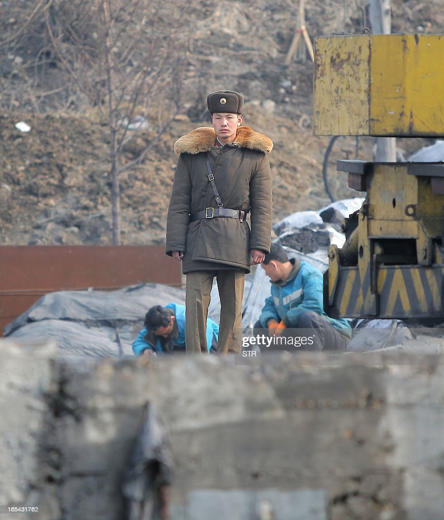 A North Korean soldier stands guard as dock workers rest along the bank of the Yalu River in the North Korean town of Sinuiju across from the Chinese city of Dandong on April 4, 2013. North Korea appears to have moved a medium range missile to its east coast, South Korean Defence Minister Kim Kwan-Jin said, prompting fears of a strike against South Korea or Japan. CHINA OUT AFP PHOTO