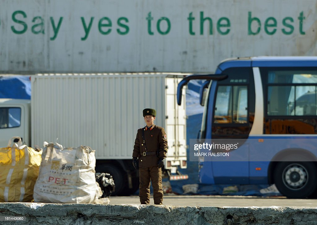 A North Korean soldier stands guard beside a shipping container on the banks of the Yalu River at the North Korean town of Sinuiju on February 11, 2013 across from the Chinese city of Dandong. A North Korean state media outlet has accused the United States of 'jumping to conclusions' that the North would soon stage a nuclear test, adding to the confusion over its immediate intentions. The US and its ally South Korea are 'fussing over speculation' without knowing exactly what action the North plans to take, Tongil Sinbo, a Japan-based pro-North weekly magazine funded by Pyongyang, said. AFP PHOTO/Mark RALSTON