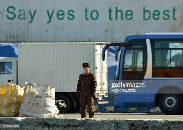 A North Korean soldier stands guard beside a shipping container on the banks of the Yalu River at the North Korean town of Sinuiju on February 11...