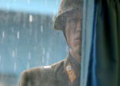 North Korean soldier stands in the rain while looking through the window of the UN truce village building that sits on the border of the...