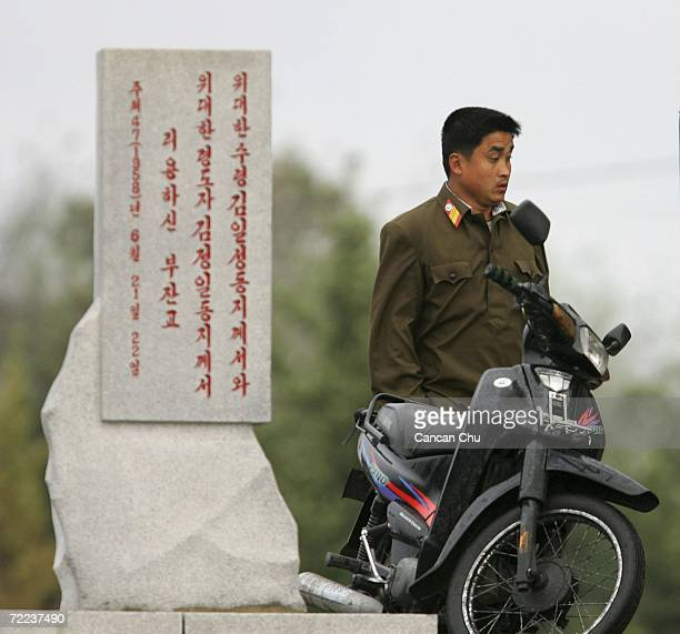 North Korean soldier stands near a motorbicycle on the banks of the Yalu River in the North Korean town of Sinuiju opposite the Chinese border city...