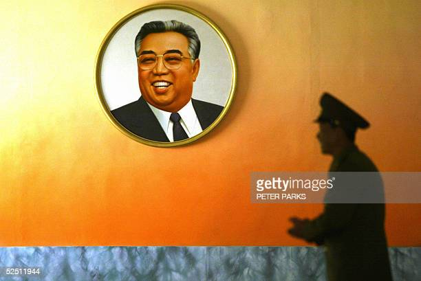 TO GO WITH STORY 'NKOREAKIMTOMB' A North Korean soldier stands next to a picture of the late leader Kim IlSung in the Demilitarized Zone at Panmunjon...