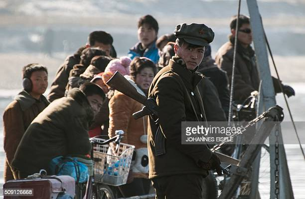A North Korean soldier stands on a boat on the Yalu River near the town of Sinuiju across from the Chinese border town of Dandong on February 9 2016...
