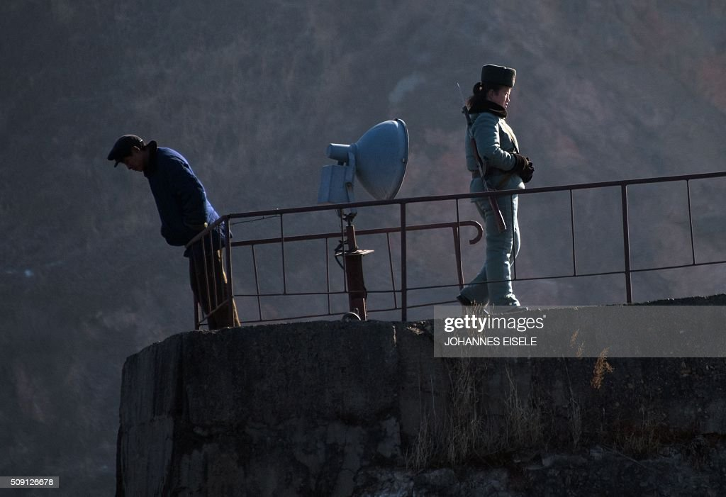 A North Korean soldier (R) stands on a wall at the banks of the Yalu River at the town of Sinuiju across from the Chinese border town of Dandong on February 9, 2016. A raft of UN sanctions imposed on North Korea over the past decade has failed to prevent Pyongyang from scaling up its nuclear and ballistic missile programs, a UN panel of experts has concluded. AFP PHOTO / JOHANNES EISELE / AFP / JOHANNES EISELE