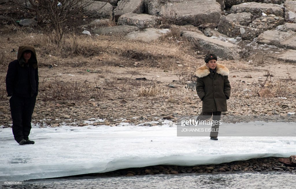 A North Korean soldier (R) stands on the banks of the Yalu River at the town of Sinuiju across from the Chinese border town of Dandong on February 8, 2016. The UN Security Council strongly condemned North Korea's rocket launch on February 7 and agreed to move quickly to impose new sanctions that will punish Pyongyang for 'these dangerous and serious violations.' AFP PHOTO / JOHANNES EISELE / AFP / JOHANNES EISELE