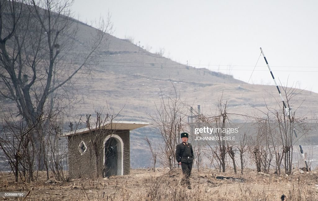 A North Korean soldier stands on the banks of the Yalu River in the North Korean town of Sinuiju, in an image taken from across the river in the Chinese border town of Dandong on February 8, 2016. The UN Security Council strongly condemned North Korea's rocket launch on February 7 and agreed to move quickly to impose new sanctions that will punish Pyongyang for 'these dangerous and serious violations.' With backing from China, Pyongyang's ally, the council again called for 'significant measures' during an emergency meeting held after North Korea said it had put a satellite into orbit with a rocket launch. AFP PHOTO / JOHANNES EISELE / AFP / JOHANNES EISELE