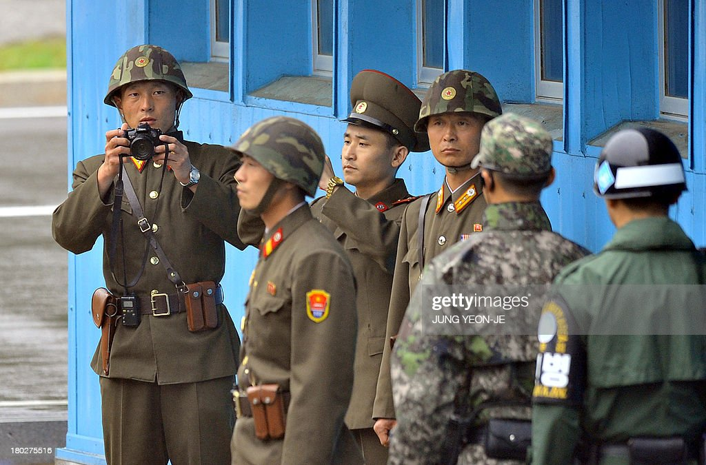 A North Korean soldier (L) takes a photo of southern side during a repatriation ceremony for the body of a North Korean soldier, who was found dead in the Han river near the border in July, during a repatriation ceremony at the truce village of Panmunjom in the Demilitarized zone dividing the two Koreas on September 11, 2013. The ceremony was supervised by United Nations officials who have been monitoring the truce since the 1950-53 Korean War.