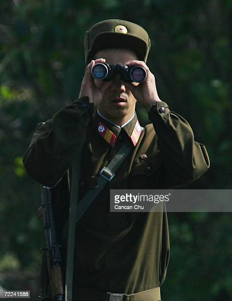 North Korean soldier uses a telescope as he patrols along the banks of the Yalu River in the North Korean town of Sinuiju opposite the Chinese border...
