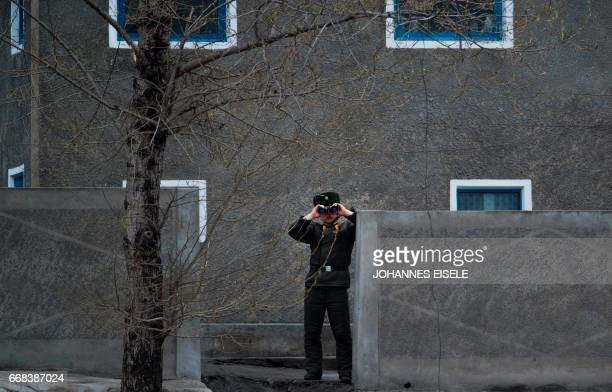 A North Korean soldier uses his binoculars to look across the Yalu river near Sinuiju opposite the Chinese border city of Dandong on April 14 2017 A...