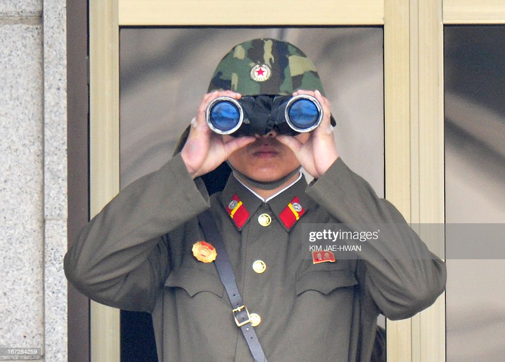 A North Korean soldier using binoculars watches from his quarters at the truce village of Panmunjom in the demilitarised zone on April 23, 2013. Tensions simmer along the world's last Cold War frontier after weeks of hostile threats from North Korea and its preparations for potential missile launches. AFP PHOTO / KIM JAE-HWAN