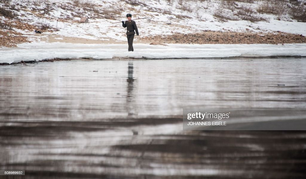 A North Korean soldier walks along the banks of the Yalu River in the North Korean town of Sinuiju, in an image taken from across the river in the Chinese border town of Dandong on February 8, 2016. The UN Security Council strongly condemned North Korea's rocket launch on February 7 and agreed to move quickly to impose new sanctions that will punish Pyongyang for 'these dangerous and serious violations.' With backing from China, Pyongyang's ally, the council again called for 'significant measures' during an emergency meeting held after North Korea said it had put a satellite into orbit with a rocket launch. AFP PHOTO / JOHANNES EISELE / AFP / JOHANNES EISELE