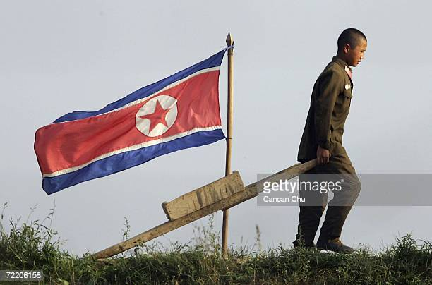 North Korean soldier walks near a North Korean flag on the outskirts of the North Korean city of Sinuiju in this picture taken on October 18 2006 in...