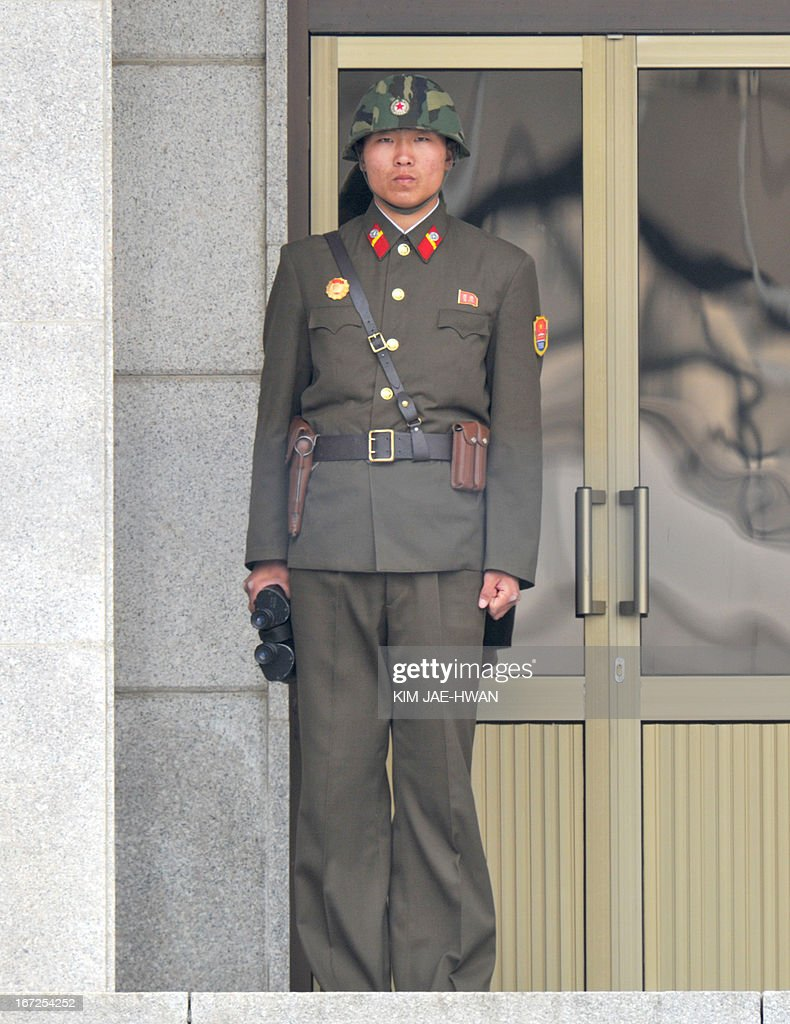 A North Korean soldier with binoculars stands on guard outside his quarters at the truce village of Panmunjom in the demilitarised zone on April 23, 2013. Tensions simmer along the world's last Cold War frontier after weeks of hostile threats from North Korea and its preparations for potential missile launches. AFP PHOTO / KIM JAE-HWAN