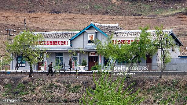 North Korean soldiers carrying rifles walk by a North Korean trainstation showing the portrait of NorthKorean leader Kim JongIl and the slogan 'Hail...