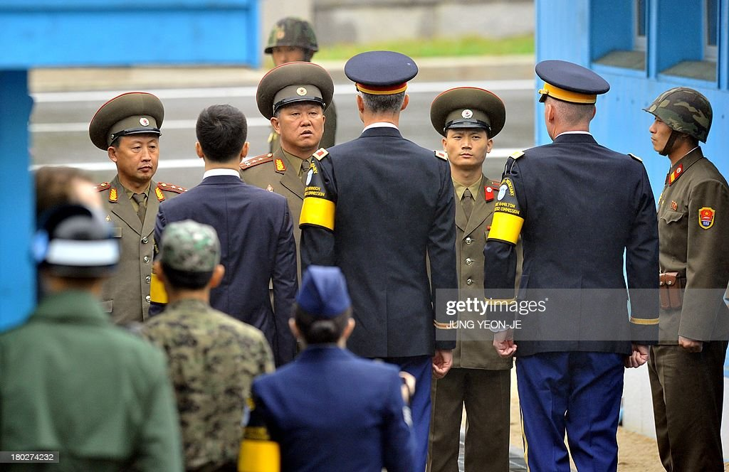 North Korean soldiers cross the border line to check a coffin containing the body of a North Korean soldier, who was found dead in the Han river near the border in July, during a repatriation ceremony at the truce village of Panmunjom in the Demilitarized zone dividing the two Koreas on September 11, 2013. The ceremony was supervised by United Nations officials who have been monitoring the truce since the 1950-53 Korean War. AFP PHOTO / JUNG YEON-JE