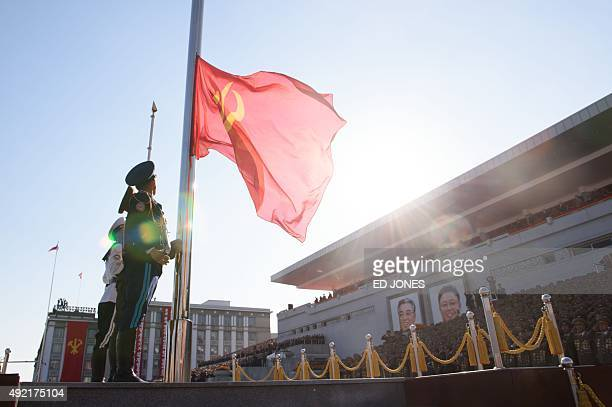 North Korean soldiers hoist a flag at the start of a mass military parade at Kim IlSung square in Pyongyang on October 10 2015 North Korea was...