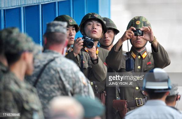 North Korean soldiers look at the South side as government delegations from the UN allied nations visit the truce village of Panmunjom in the...