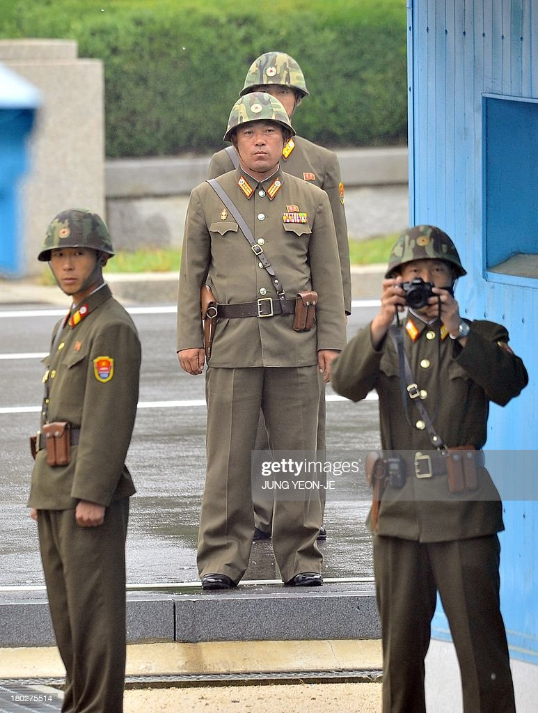 North Korean soldiers look at the South side during a repatriation ceremony for the body of a North Korean soldier, who was found dead in the Han river near the border in July, during a repatriation ceremony at the truce village of Panmunjom in the Demilitarized zone dividing the two Koreas on September 11, 2013. The ceremony was supervised by United Nations officials who have been monitoring the truce since the 1950-53 Korean War.