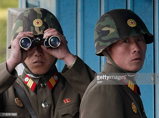 North Korean soldiers look at the southern side as US Commerce Secretary Gary Locke and members of the House of Representatives visit to the border...