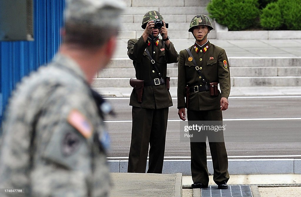 North Korean soldiers look on as Korean War veterans and officials visit to commemorate the 60th Anniversary of the Korean War Armistice Agreement by United Nations Command (UNC) and Neutral Nations Supervisory Commission (NNSC) on July 27, 2013 in Panmunjom, South Korea. On June 25, 1950, soldiers of the North Korean army breached the 38th parallel invading the Republic of South Korea, marking the beginning of the Korean War. On July 27, 1953, a signed armistice agreement brought the three-year conflict to an end.