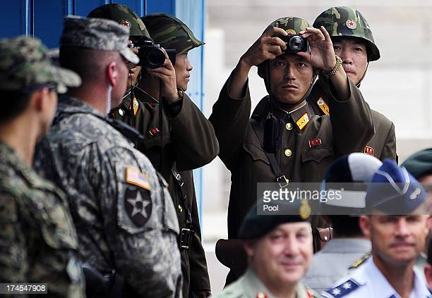 North Korean soldiers look on as Korean War veterans and officials visit to commemorate the 60th Anniversary of the Korean War Armistice Agreement by...