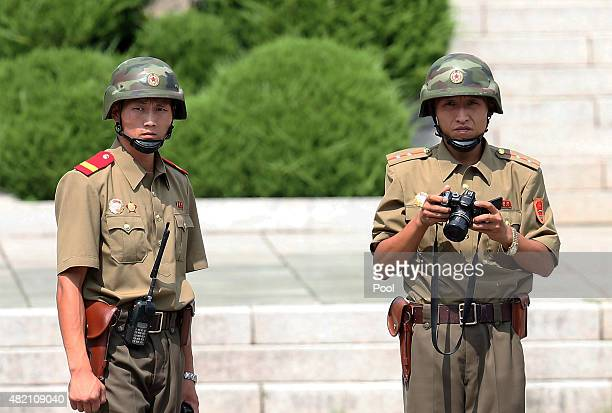 North Korean soldiers look on as South Korean and United Nation officials visit after attending a ceremony to commemorate the 62nd Anniversary of the...