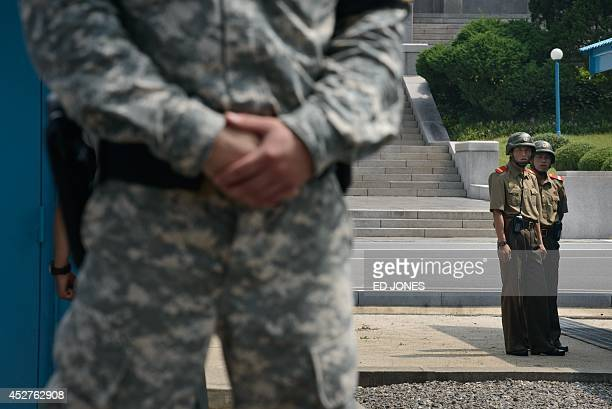 North Korean soldiers look towards a US soldier standing before the military demarcation line seperating North and South Korea within the Joint...