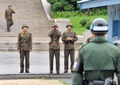 North Korean soldiers look towards South side as a South Korean soldier stands guard while Army General James Thurman new commander of US forces in...