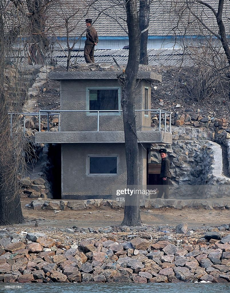 North Korean soldiers man a watch tower along the bank of the Yalu River in the North Korean town of Sinuiju across from the Chinese city of Dandong on April 4, 2013. North Korea appears to have moved a medium range missile to its east coast, South Korean Defence Minister Kim Kwan-Jin said, prompting fears of a strike against South Korea or Japan. CHINA OUT AFP PHOTO