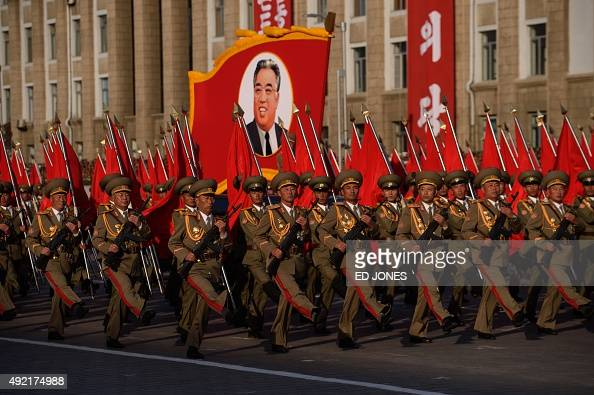 North Korean soldiers march with a portrait of late leader Kim IlSung during a mass military parade at Kim IlSung square in Pyongyang on October 10...