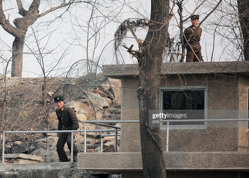 North Korean soldiers on the lookout at a watch tower along the bank of the Yalu River in the North Korean town of Sinuiju across from the Chinese city of Dandong on April 4, 2013. North Korea appears to have moved a medium range missile to its east coast, South Korean Defence Minister Kim Kwan-Jin said, prompting fears of a strike against South Korea or Japan. CHINA OUT AFP PHOTO