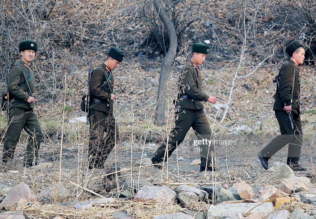 North Korean soldiers patrol along the bank of the Yalu River in the North Korean town of Sinuiju across from the Chinese city of Dandong on April 4, 2013. North Korea appears to have moved a medium range missile to its east coast, South Korean Defence Minister Kim Kwan-Jin said, prompting fears of a strike against South Korea or Japan. CHINA OUT AFP PHOTO