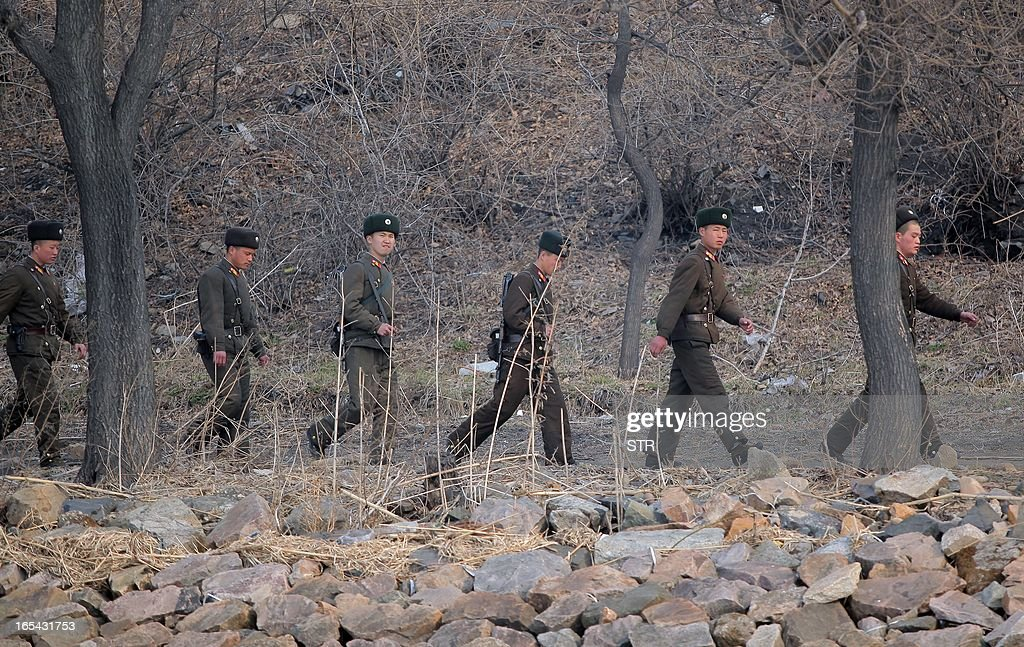 North Korean soldiers patrol along the bank of the Yalu River in the North Korean town of Sinuiju across from the Chinese city of Dandong on April 4, 2013. North Korea appears to have moved a medium range missile to its east coast, South Korean Defence Minister Kim Kwan-Jin said, prompting fears of a strike against South Korea or Japan. CHINA