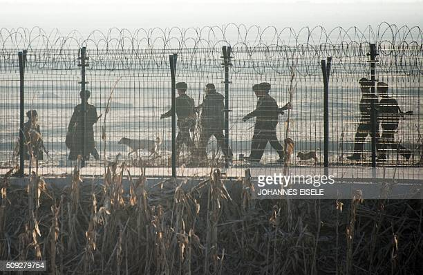 North Korean soldiers patrol next to the border fence near the town of Sinuiju across from the Chinese border town of Dandong on February 10 2016...