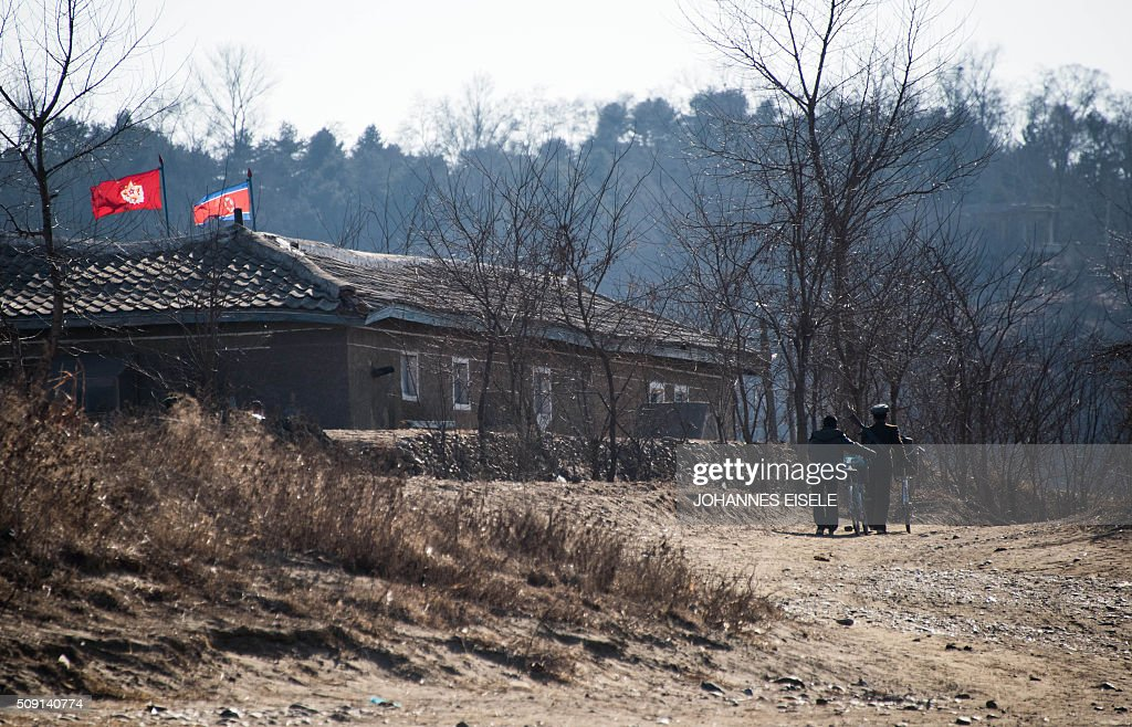 North Korean soldiers push their bikes on a road next the Yalu River in the North Korean town of Sinuiju, as seen from across the river from the Chinese border town of Dandong on February 9, 2016. The rocket launched by North Korea at the weekend seemed more powerful than its 2012 predecessor, but Pyongyang still lacks the expertise to transform it into a ballistic missile capable of reaching the US mainland, South Korean officials said on February 9. AFP PHOTO / JOHANNES EISELE / AFP / JOHANNES EISELE