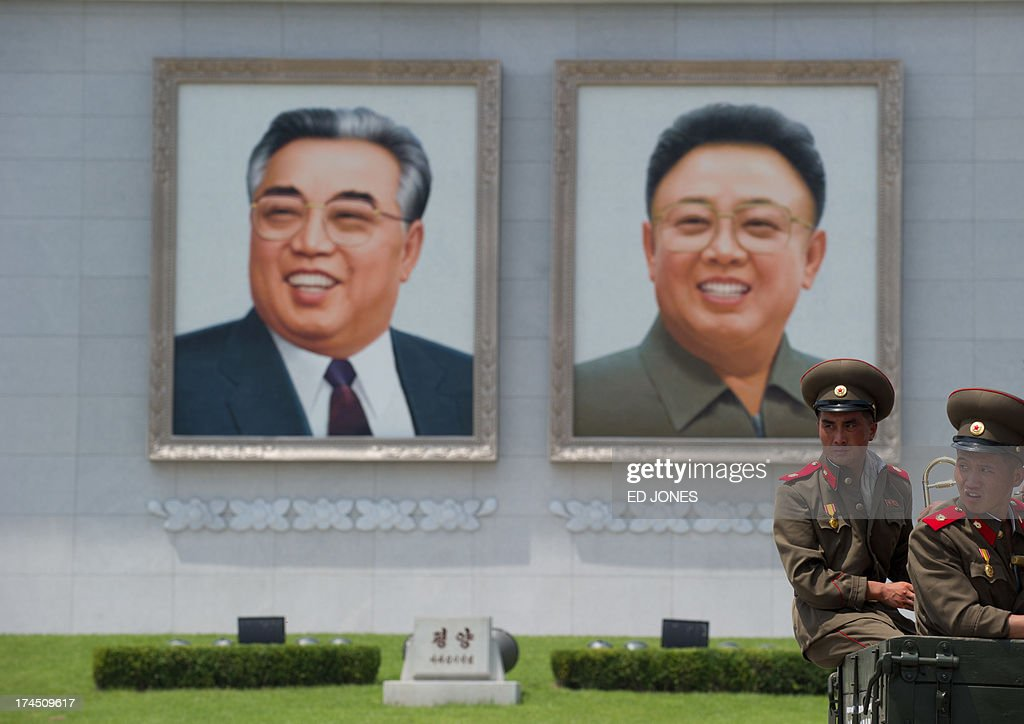 North Korean soldiers sit on the back of a truck on Kim Il-Sung square before portraits of former leaders Kim Il-Sung (L) and Kim Jong-Un (R) as they wait to leave a parade marking the 60th anniversary of the Korean war armistice in Pyongyang on July 27, 2013. North Korea mounted its largest ever military parade on July 27 to mark the 60th anniversary of the armistice that ended fighting in the Korean War, displaying its long-range missiles at a ceremony presided over by leader Kim Jong-Un. AFP PHOTO / Ed Jones