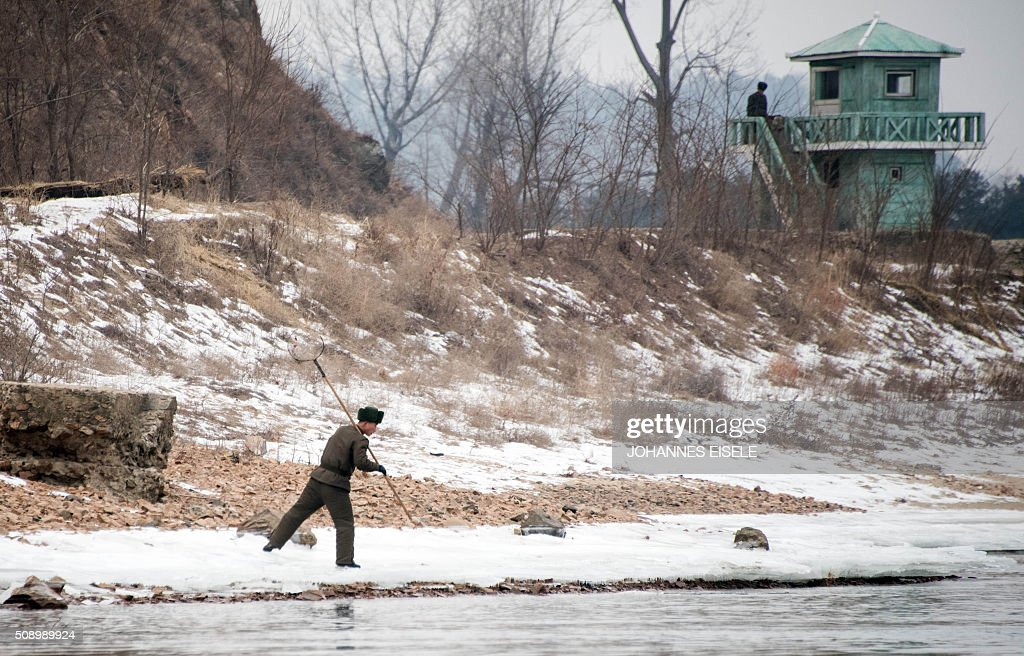 North Korean soldiers stand at their watchtower (R) as another walks on the banks of the Yalu River in the North Korean town of Sinuiju, in an image taken from across the river in the Chinese border town of Dandong on February 8, 2016. The UN Security Council strongly condemned North Korea's rocket launch on February 7 and agreed to move quickly to impose new sanctions that will punish Pyongyang for 'these dangerous and serious violations.' With backing from China, Pyongyang's ally, the council again called for 'significant measures' during an emergency meeting held after North Korea said it had put a satellite into orbit with a rocket launch. AFP PHOTO / JOHANNES EISELE / AFP / JOHANNES EISELE