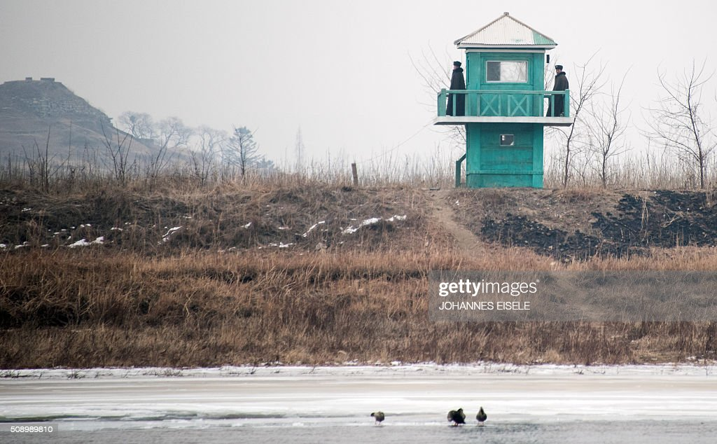 North Korean soldiers stand at their watchtower on the banks of the Yalu River in the North Korean town of Sinuiju, in an image taken from across the river in the Chinese border town of Dandong on February 8, 2016. The UN Security Council strongly condemned North Korea's rocket launch on February 7 and agreed to move quickly to impose new sanctions that will punish Pyongyang for 'these dangerous and serious violations.' With backing from China, Pyongyang's ally, the council again called for 'significant measures' during an emergency meeting held after North Korea said it had put a satellite into orbit with a rocket launch. AFP PHOTO / JOHANNES EISELE / AFP / JOHANNES EISELE