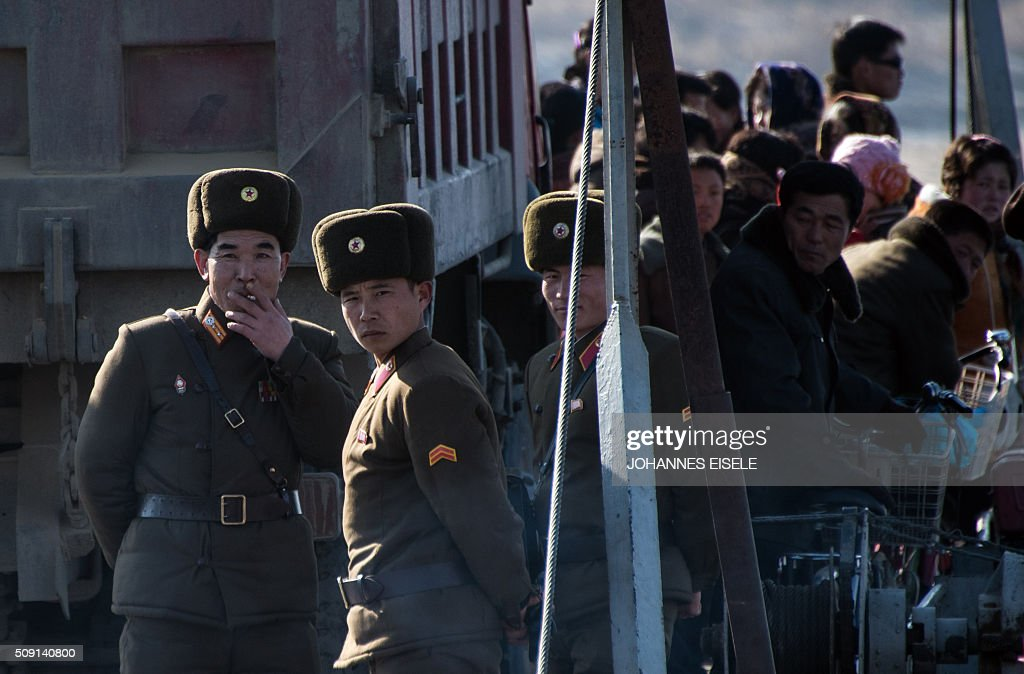 North Korean soldiers stand on a boat on the Yalu River in the North Koreantown of Sinuiju, as seen from across the river from the Chinese border town of Dandong on February 9, 2016. The rocket launched by North Korea at the weekend seemed more powerful than its 2012 predecessor, but Pyongyang still lacks the expertise to transform it into a ballistic missile capable of reaching the US mainland, South Korean officials said on February 9. AFP PHOTO / JOHANNES EISELE / AFP / JOHANNES EISELE
