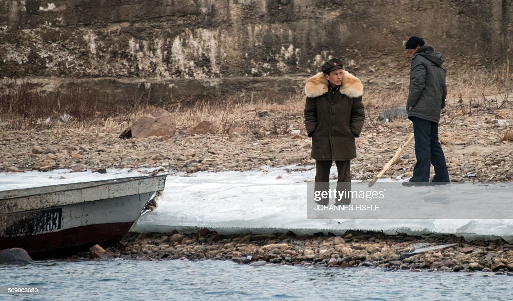 North Korean soldiers stand on the banks of the Yalu River at the town of Sinuiju across from the Chinese border town of Dandong on February 8, 2016. The UN Security Council strongly condemned North Korea's rocket launch on February 7 and agreed to move quickly to impose new sanctions that will punish Pyongyang for 'these dangerous and serious violations.' AFP PHOTO / JOHANNES EISELE / AFP / JOHANNES EISELE