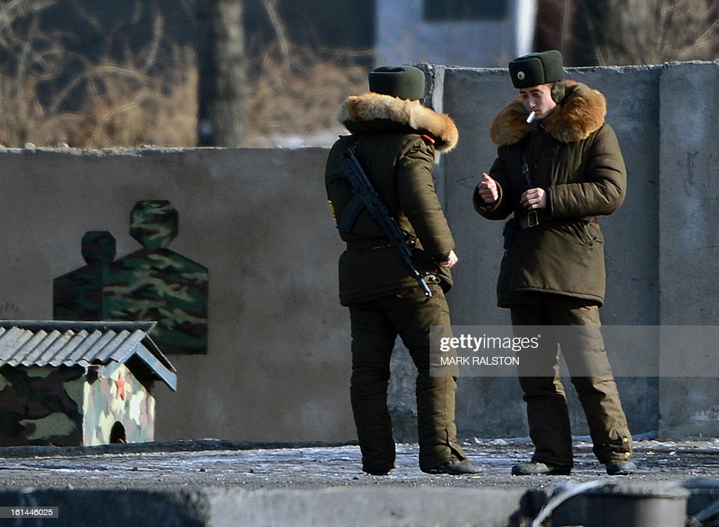 North Korean soldiers stand outside their barracks on the banks of the Yalu River at the North Korean town of Sinuiju on February 11, 2013 across from the Chinese city of Dandong. A North Korean state media outlet has accused the United States of 'jumping to conclusions' that the North would soon stage a nuclear test, adding to the confusion over its immediate intentions. The US and its ally South Korea are 'fussing over speculation' without knowing exactly what action the North plans to take, Tongil Sinbo, a Japan-based pro-North weekly magazine funded by Pyongyang, said. AFP PHOTO/Mark RALSTON