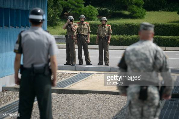 North Korean soldiers take photos towards a South Korean soldier and a US soldier standing before the military demarcation line seperating North and...