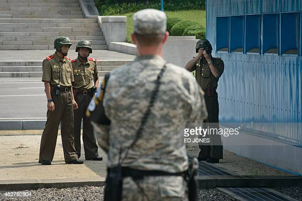 North Korean soldiers take photos towards a US soldier standing before the military demarcation line seperating North and South Korea within the...
