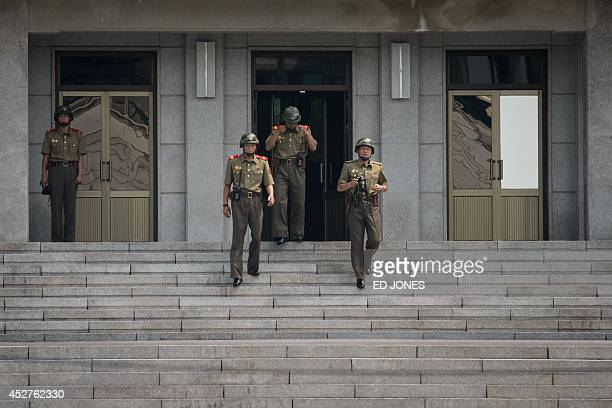 North Korean soldiers walk down the steps towards the military demarcation line within the Joint Security Area at Panmunjom on July 27 2014 South...