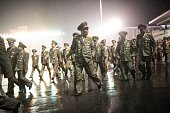 North Korean soldiers walk during rainfall following a mass military parade at Kim IlSung square in Pyongyang on October 10 2015 North Korea was...
